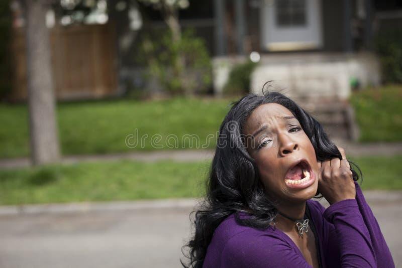 Mulher americana africana nova horrorizada na parte superior roxa imagem de stock royalty free