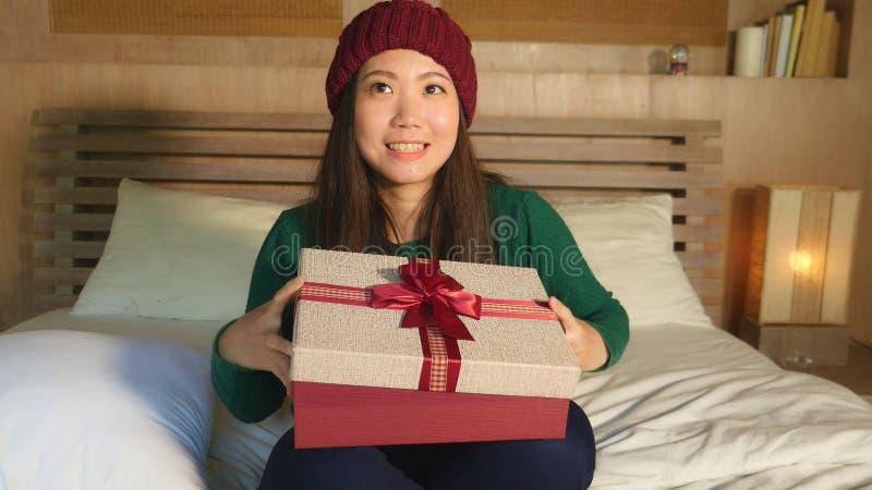 Mulher americana asiática bonita feliz nova no chapéu do inverno que guarda o giftbox do Natal com fita que sorri receiv entusias fotos de stock