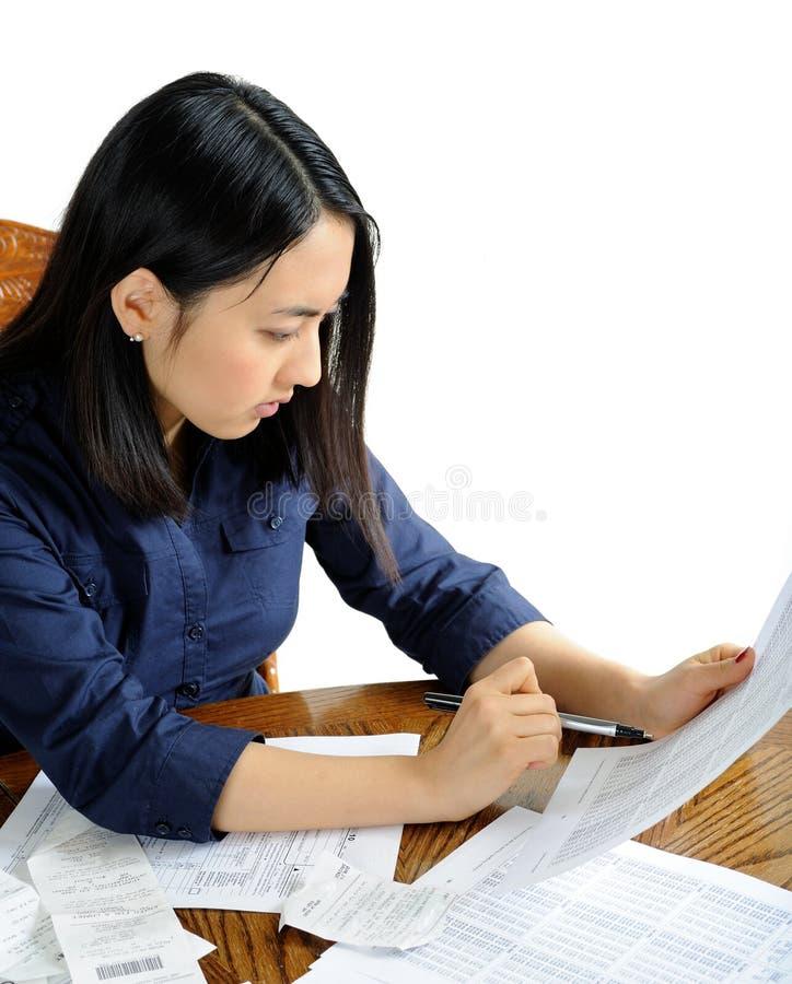 Mulher americana asiática que trabalha em impostos imagem de stock royalty free