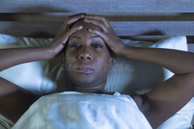 Mulher americana assustado e forçada nova do africano negro comprimida em incapaz virado da cama de dormir sentimento de sofrimen fotos de stock royalty free