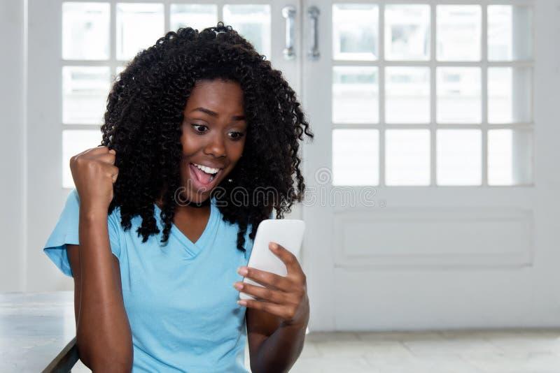 Mulher americana bonita de África que recebe a boa notícia no telefone imagens de stock royalty free