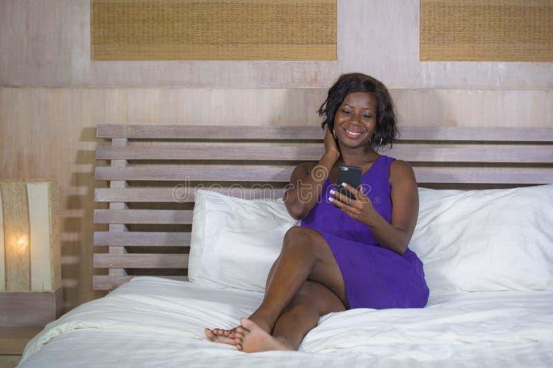 Mulher americana do africano negro feliz que senta-se na cama usando o telefone celular do Internet que sorri trabalhos em rede a imagem de stock royalty free
