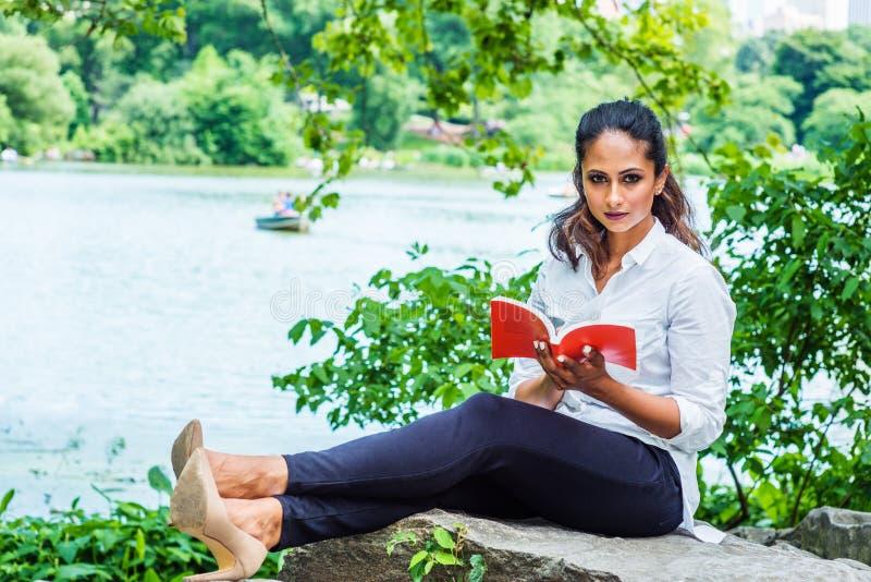 Mulher americana indiana do leste nova que lê o livro vermelho, relaxando no Central Park, New York imagem de stock royalty free