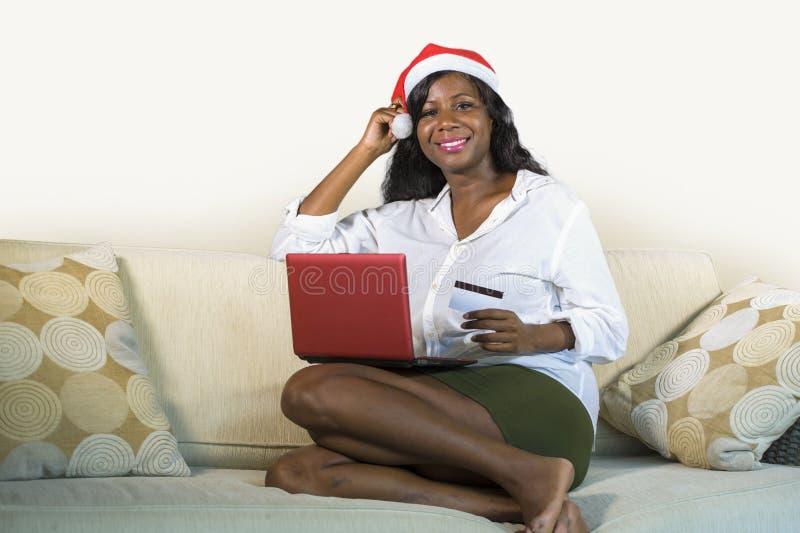 Mulher americana nova do africano negro feliz e atrativo em Santa Claus que usa o cartão e o portátil de crédito para a compra em fotografia de stock