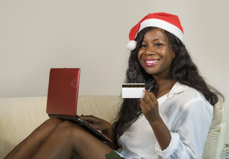 Mulher americana nova do africano negro feliz e atrativo no chapéu de Santa Claus que guarda o presente de Natal da compra do car foto de stock royalty free