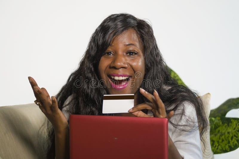 Mulher americana nova do africano negro feliz e atrativo que usa a operação bancária do cartão e do laptop de crédito em linha e  imagens de stock
