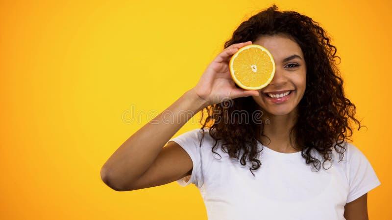 Mulher americana saudável que guarda a meia parte dianteira alaranjada do olho, das vitaminas e do bem-estar fotos de stock royalty free