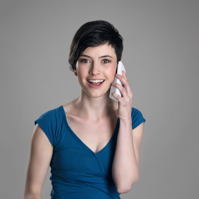 Mulher amigável de sorriso do cabelo curto que fala no telefone celular que olha a câmera fotografia de stock royalty free