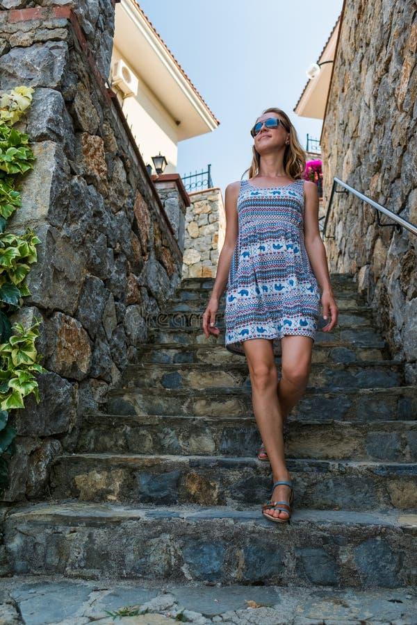 A mulher anda abaixo das escadas telhadas fotografia de stock