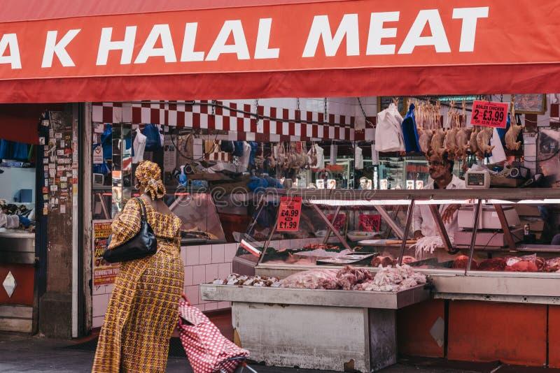 A mulher anda após a loja Halal da carne em Brixton Market, Londres, Reino Unido imagem de stock royalty free