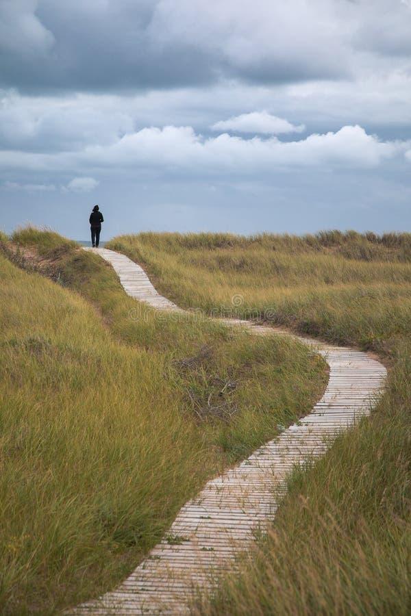 A mulher anda as dunas de Iles de la Madeleine fotografia de stock royalty free