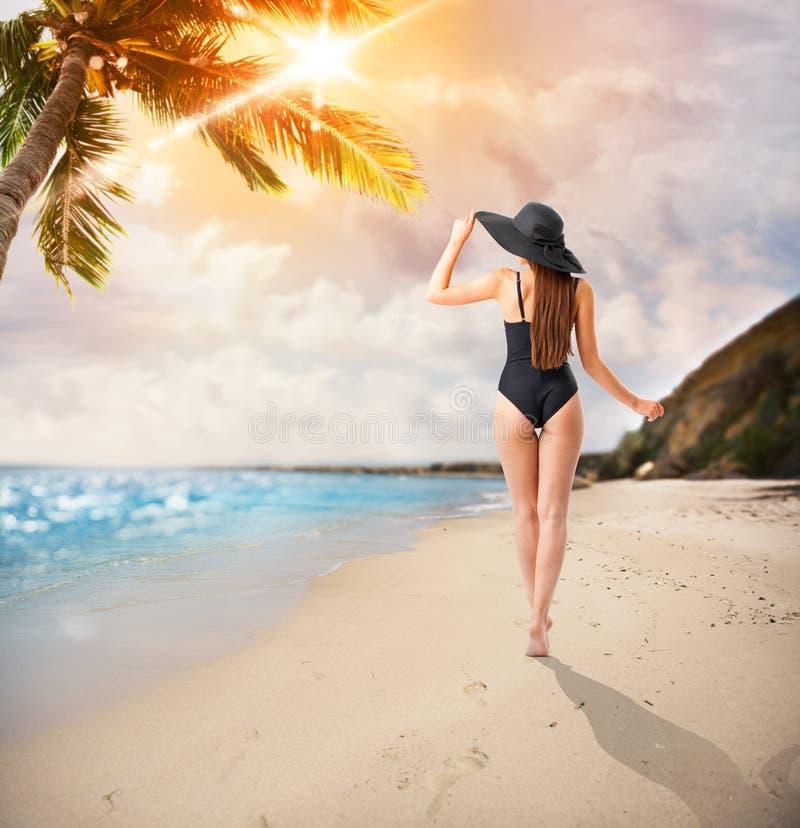 A mulher anda em uma praia tropical fotos de stock