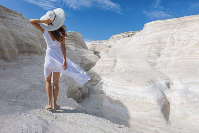 A mulher anda nas formações de rocha vulcânica de Sarakiniko, Milos ilha, Grécia imagem de stock