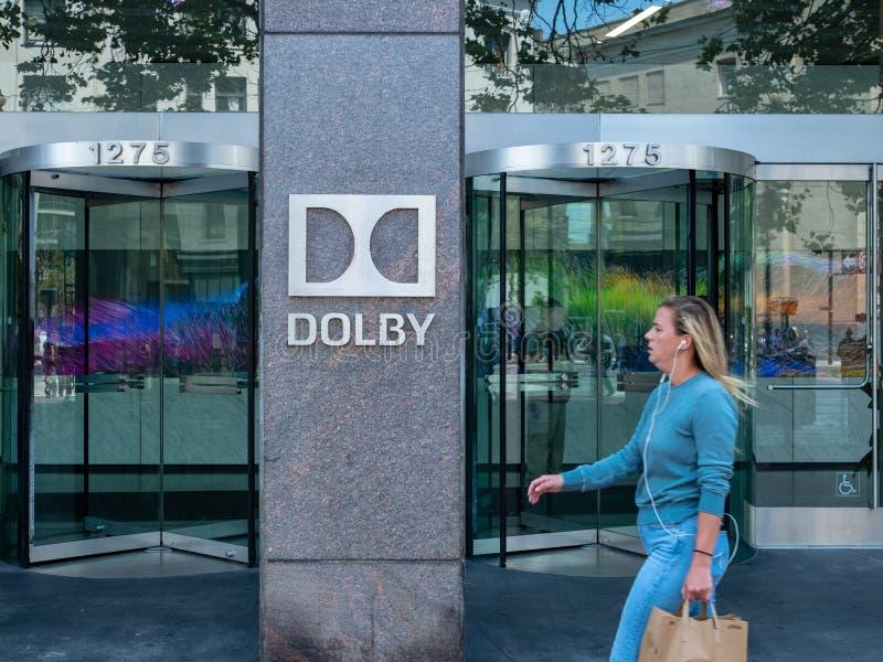 A mulher anda pelo sinal das matrizes dos laboratórios de Dolby imagem de stock royalty free