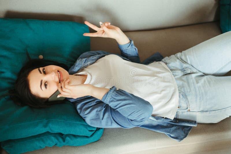 Mulher animada falando no celular em casa fotografia de stock