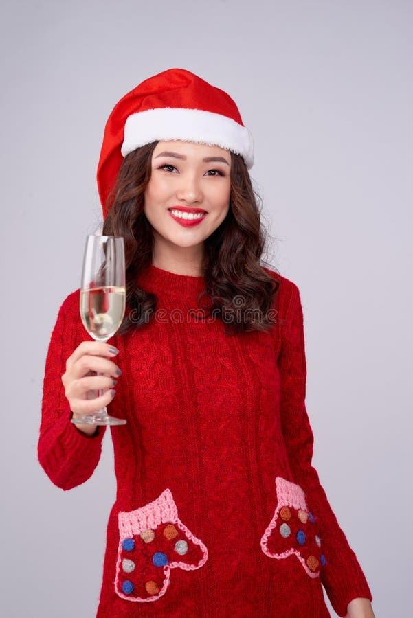 Mulher animada usando chapéu de natal e vestido segurando vidro de champanhe imagens de stock royalty free