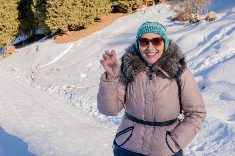 Mulher 50 anos de caminhada velha nas montanhas no inverno, Almaty, Ka fotografia de stock royalty free
