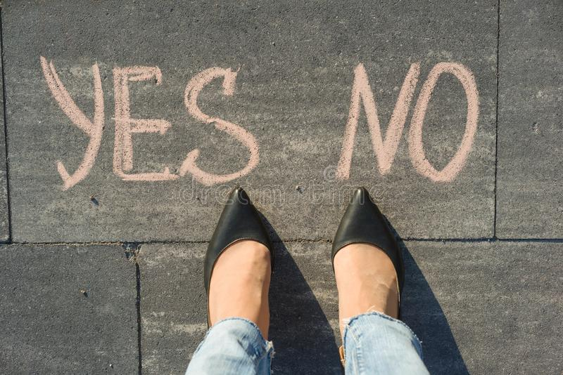 Mulher antes da escolha sim ou do não Vista de cima de, pés fêmeas com do texto o nenhum sim escrito no passeio cinzento imagem de stock