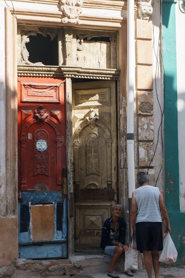 Mulher antiga situada na parte dianteira da porta em uma casa velha do La Havana, Cuba fotos de stock