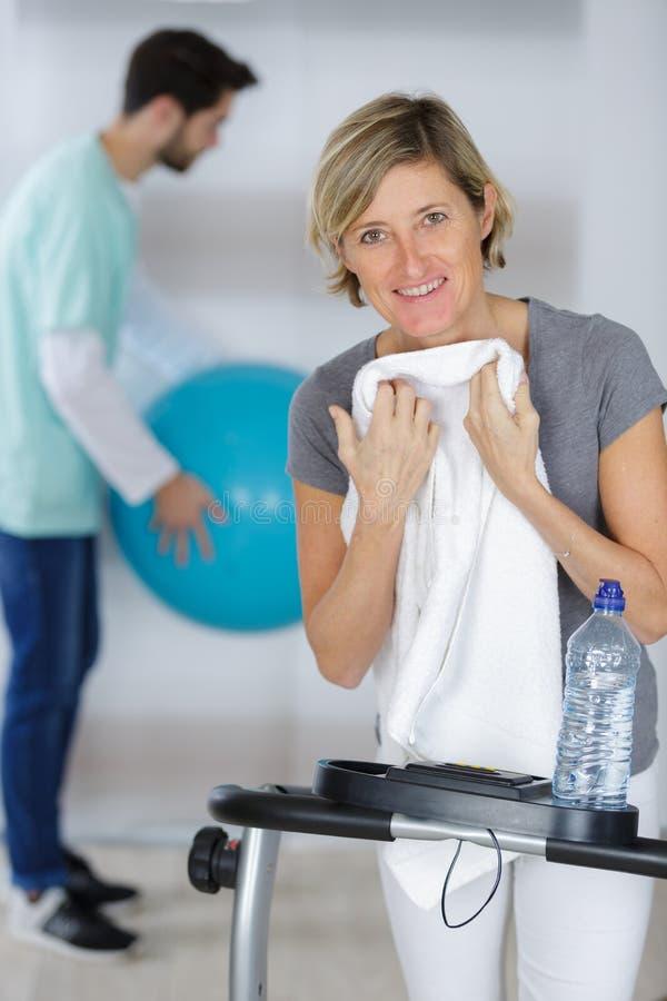 Mulher após o exercício com o fisioterapeuta novo experiente imagem de stock royalty free
