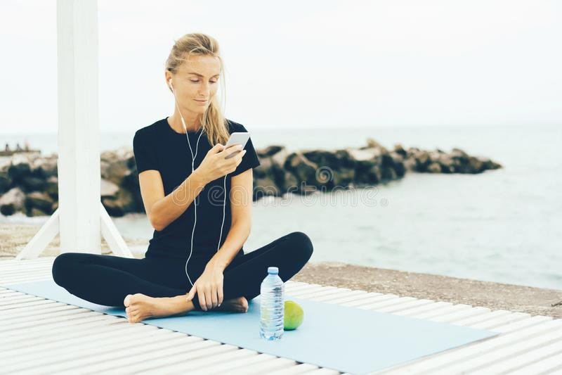 Mulher após o exercício com um telefone em suas mãos foto de stock