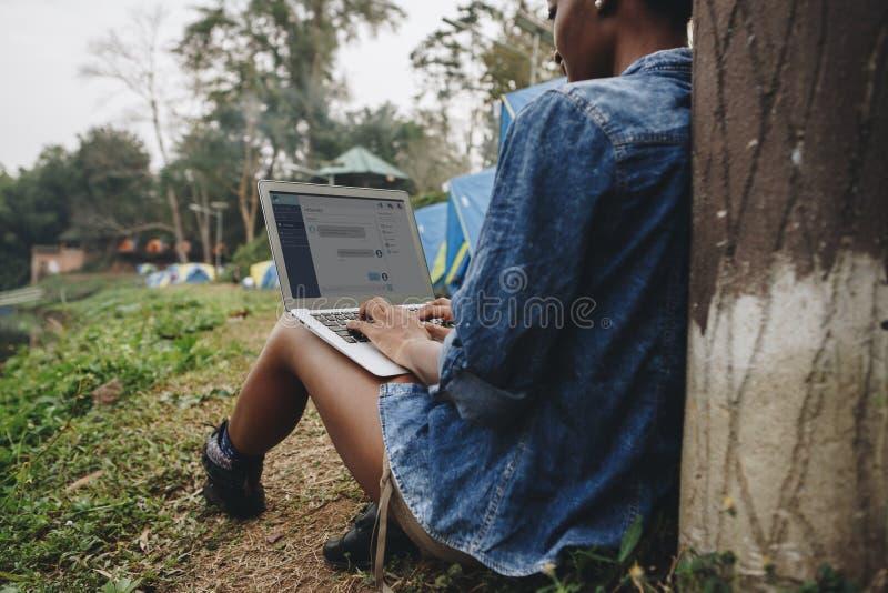 Mulher apenas na natureza usando um portátil em uma fuga do local de acampamento do trabalho ou do conceito do apego do Internet imagem de stock