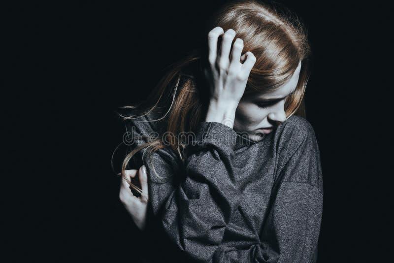 Mulher apenas na sala escura fotografia de stock royalty free