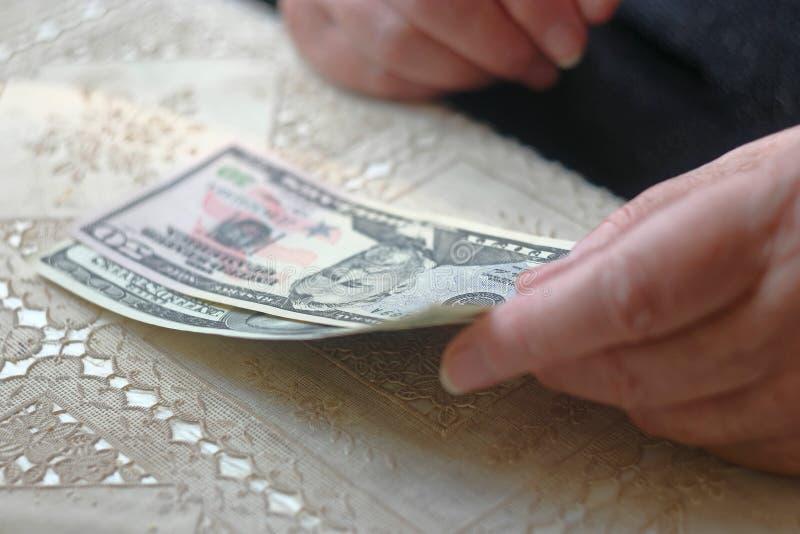Mulher aposentada com pequena quantidade de dinheiro na tabela, imagem tonificada, foco colorized, seletivo, dof muito raso sênio fotografia de stock royalty free