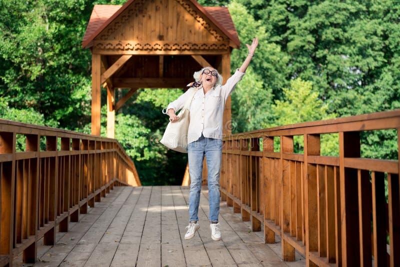 Mulher aposentada feliz que salta ao apreciar o turismo agradável do eco fotos de stock