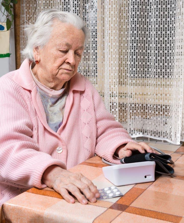 Mulher aposentada idosa que toma a pressão sanguínea imagem de stock