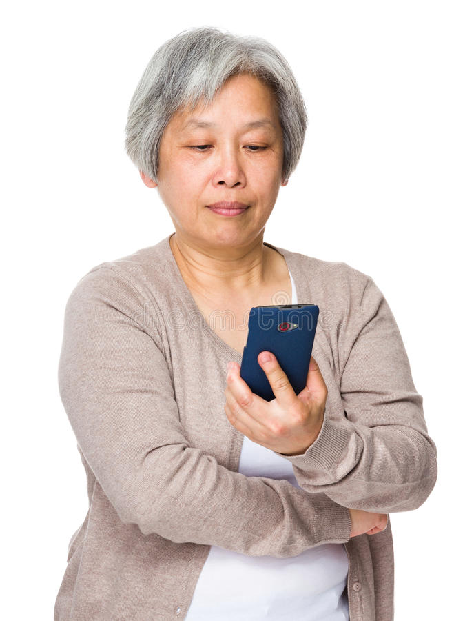 Mulher aposentada lida no telefone celular fotos de stock royalty free