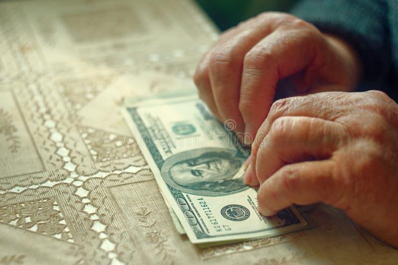Mulher aposentada sênior com pequena quantidade de dinheiro na tabela, imagem tonificada, foco colorized, seletivo, dof muito ras foto de stock