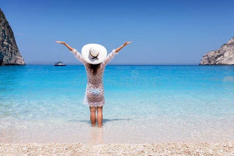 A mulher aprecia as águas azuis da praia do naufrágio na ilha de Zakynthos, Grécia imagens de stock