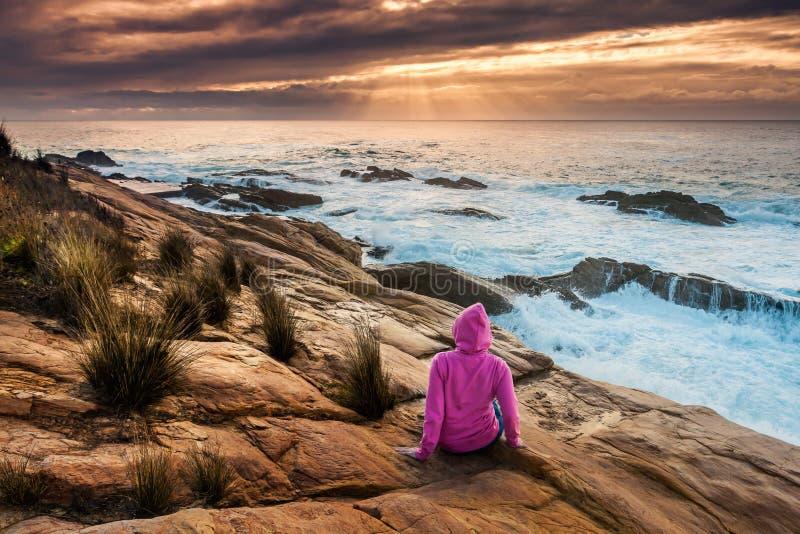 A mulher aprecia ideias dos raios de sol e dos fluxos do mar imagens de stock royalty free