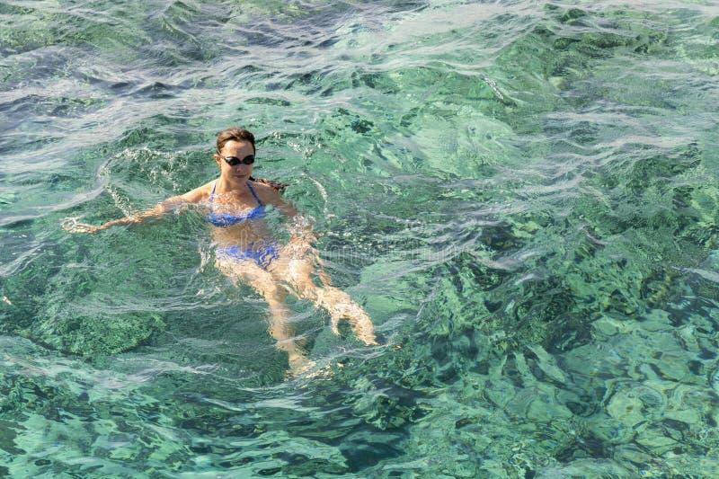 a mulher aprecia nadar no mar Nadadas da jovem mulher no mar A menina dos esportes nada no mar imagem de stock royalty free