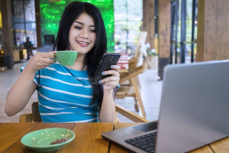 A mulher aprecia o café ao texting no café foto de stock royalty free