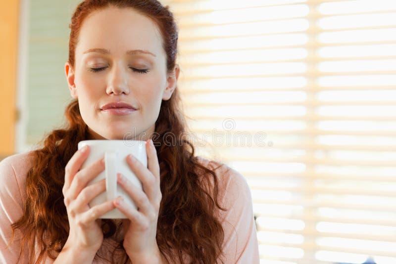 A mulher aprecia o cheiro de seu café imagens de stock royalty free
