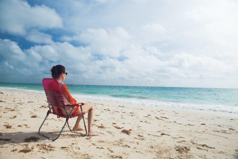 A mulher aprecia o dia na praia foto de stock