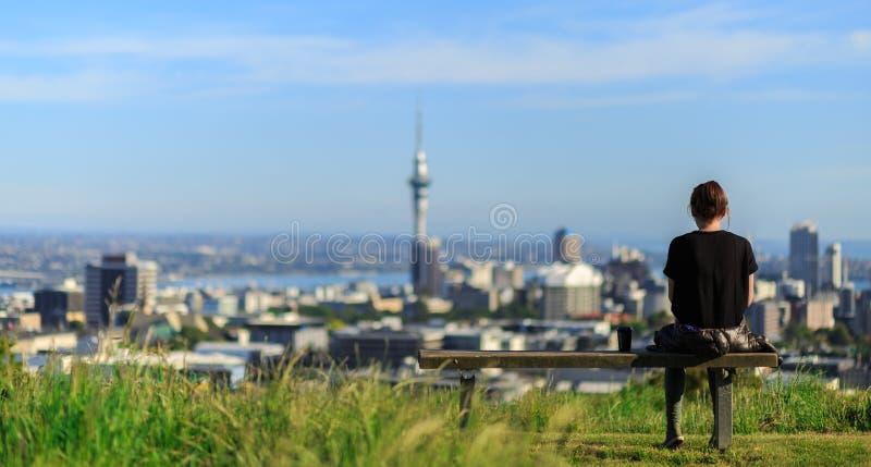 A mulher aprecia opiniões espetaculares da manhã da cidade de Auckland fotos de stock