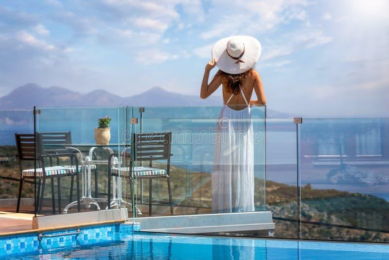 A mulher aprecia a paisagem mediterrânea em Grécia na borda de uma associação foto de stock