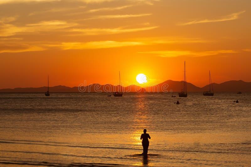 A mulher aprecia um por do sol lindo em uma praia tropical e toma uma foto Silhueta da menina que que olha o sol Tons dourados E foto de stock