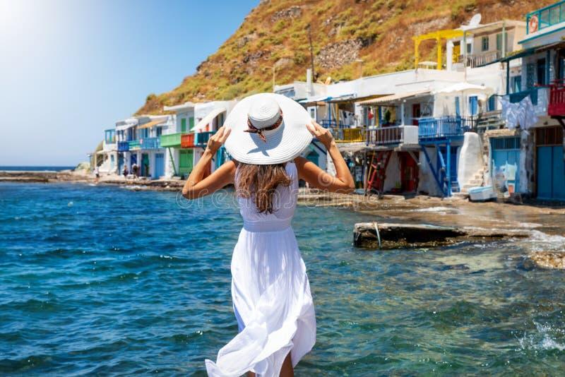 A mulher aprecia a vista à aldeia piscatória de Klima na ilha grega dos Milos fotos de stock