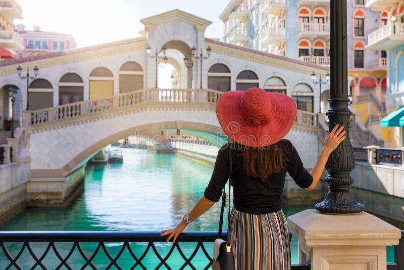 A mulher aprecia a vista ao Qanat Quartier na pérola em Doha foto de stock