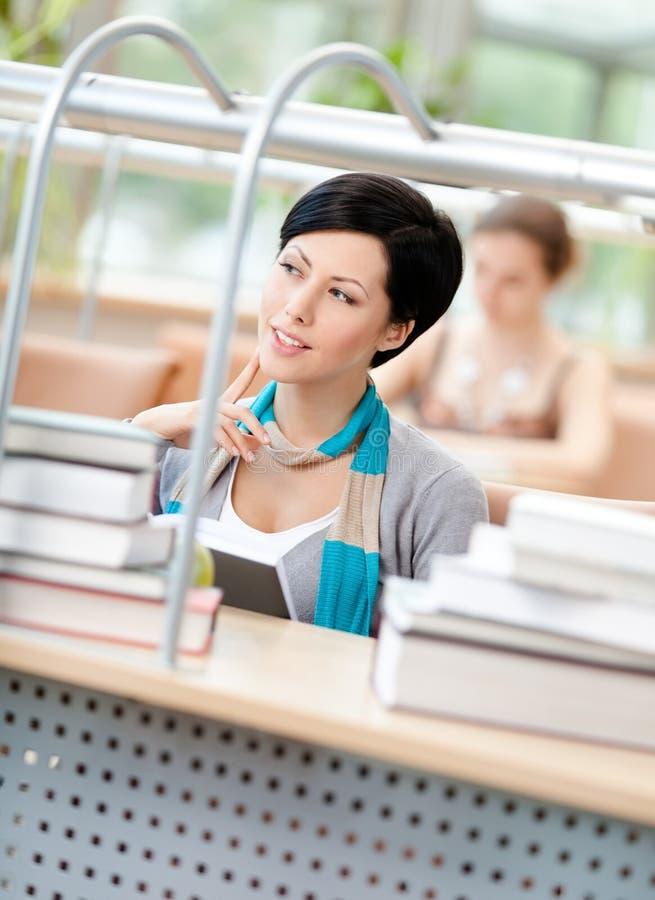 A mulher aprende no salão da leitura fotografia de stock