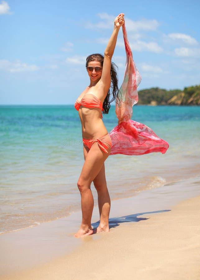 Mulher apta atlética nova em suportes alaranjados do biquini e dos óculos de sol na praia, guardando o lenço que acena no vento,  fotografia de stock
