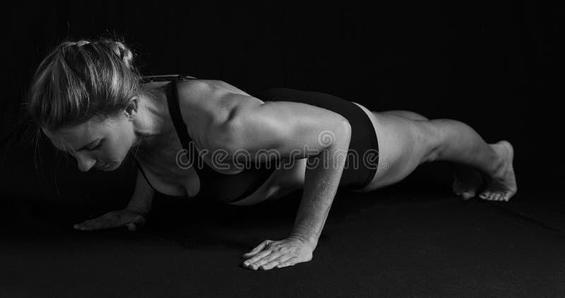 Mulher apta com os músculos dados forma no conve artístico da posição da flexão de braço imagens de stock royalty free