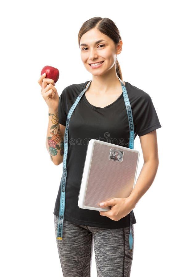 Mulher apta de sorriso dos jovens que guarda a escala de Apple e do peso foto de stock royalty free