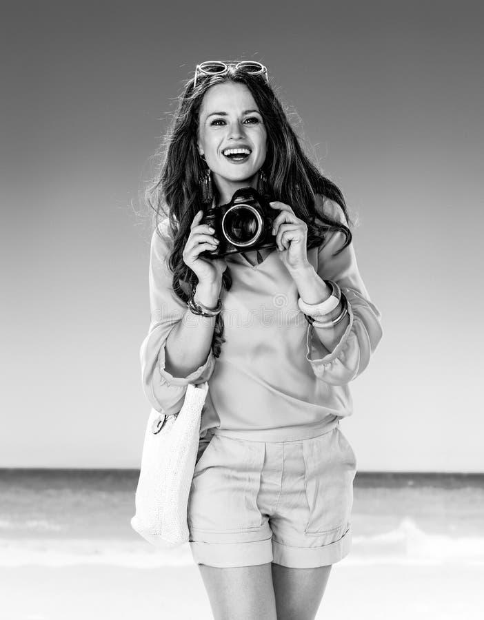 Mulher apta de sorriso no seacoast com a câmera digital de SLR imagem de stock