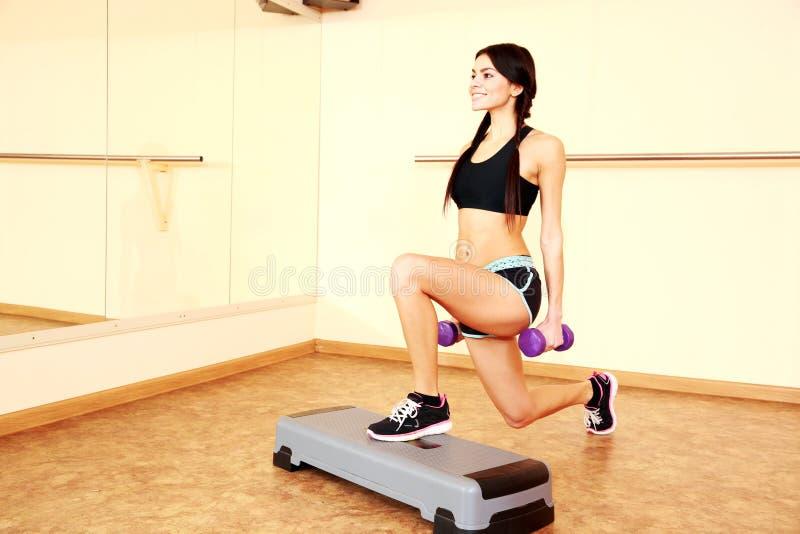 Mulher apta de sorriso nova que faz exercícios com dumbells na placa da etapa fotografia de stock