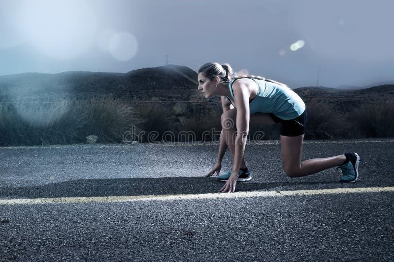 A mulher apta do esporte dos jovens que corre fora na estrada asfaltada na paisagem da montanha e na luz dramática ajustou-se anu fotos de stock
